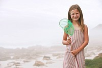 Girl 7_9 holding fishing net standing on beach portrait
