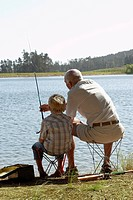 Boy 7-9 fishing with grandfather back view (thumbnail)