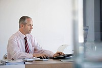 Businessman sitting at desk in office using computer.