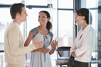 Three office workers standing in office talking