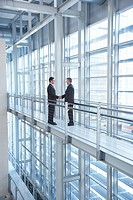 Businessmen shaking hands in modern building