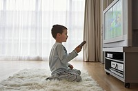 Boy 7_9 sitting on floor watching cartoons in television