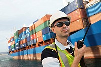 Man wearing hard hat using walkie_talkie at container terminal