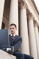 Lawyer using laptop outside courthouse