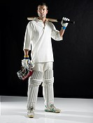 Cricket player standing holding bat on shoulder