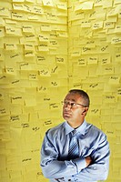Middle_aged man in glasses standing in front of wall covered in sticky notes