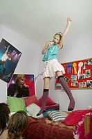 Girl jumping on bed singing friends watching from floor