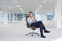Office worker sitting in swivel chair fingertips interlaced in empty office space