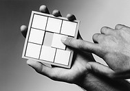 Hands holding slide puzzle b&w close-up (thumbnail)