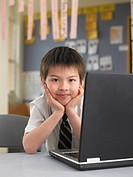 Elementary schoolboy sitting by laptop in classroom (thumbnail)