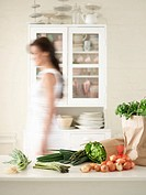 Woman walking behind Fresh Produce on Kitchen Counter side view