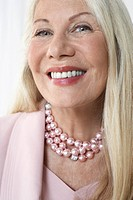 Glamorous senior woman in studio head and shoulders close up