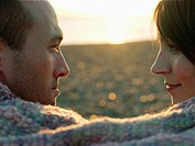 Couple face to face wrapped in blanket on beach close up