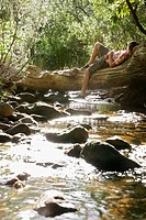 Teenage boy 16_17 years lying on tree trunk by stream in forest