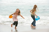 Two girls 7_9 10_12 holding buckets playing on beach