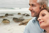 Close up of couple on beach woman resting her head on man's shoulder