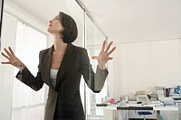 Businesswoman standing in office pressing hands and face against glass