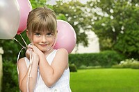 Young girl in garden holding balloons smiling portrait