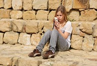 Girl texting on phone and sitting along stone wall