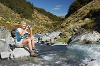 Woman taking picture of river in forest (thumbnail)