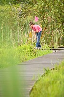 Boy Looking for Wildlife in Marsh