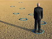 Businessman standing in hoops in desert back view full length