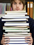 Young man holding pile of books