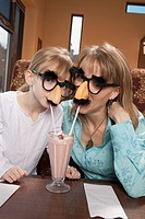 Mother and daughter share milkshake in disguise