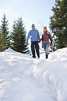 Couple descending snow_covered hill low angle view