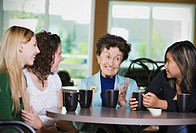 Senior woman chatting over coffee with teenage girls