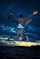 Businessman jumping for joy before sunset scene
