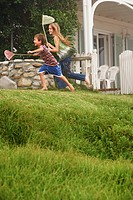 Brother and sister 5_6 10_12 holding fishing nets running in front of house