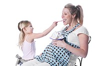 Daughter feeding ice cream to pregnant mother