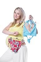 Pregnant woman holding bikini