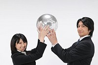 Portrait of young businessman and businesswoman holding globe, white background
