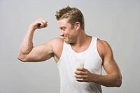 Man flexing biceps and holding a glass of milk