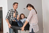 Parents lifting daughter in armchair while renovating