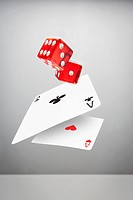 Red dice and ace playing cards in mid_air