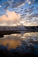 Blue sky and clouds at sunrise reflect in Firehole River, as steam rises from a geothermal area in Yellowstone Park