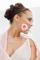 Fashion model holding rose between her teeth (thumbnail)