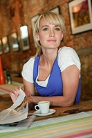Woman holding a magazine in a cafe