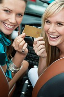 Two women showing a credit card in a car (thumbnail)