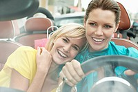 Two women sitting in a car after shopping