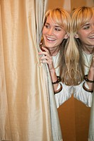 Woman peeking from behind a curtain and smiling in a boutique