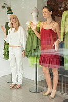 Two women imitating a mannequin in a boutique