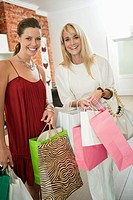 Two women holding shopping bags in a boutique and smiling