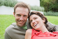 Couple resting in a lawn and smiling