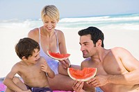 Family enjoying watermelon on the beach