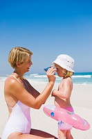 Woman putting on sunglasses on her daughter's face