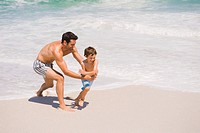 Man playing with his son on the beach